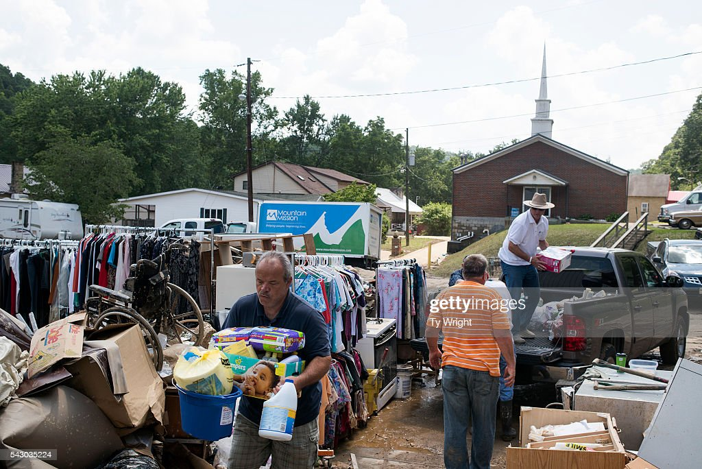 People bring in fresh supplies for community members amongst piles of water logged debris outside of the Clendenin Church of the Nazarene Community Center on June 25, 2016 in Clendenin, West Virginia. The flooding of the Elk River claimed the lives of at least 23 people in West Virginia.