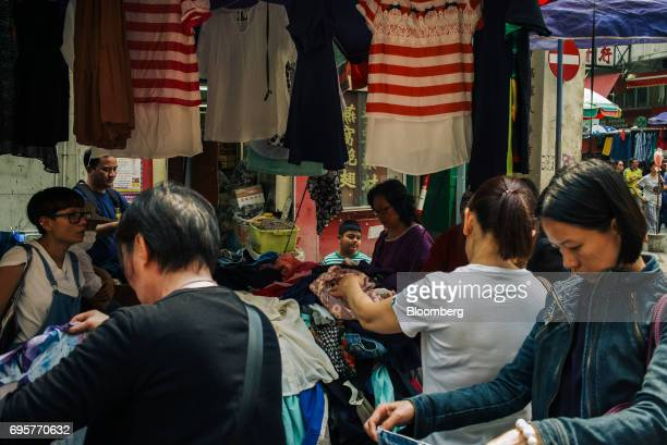 People browse clothes at a street market stall in the Sham Shui Po district of Hong Kong China on Saturday April 29 2017 Hong Kong a city of soaring...
