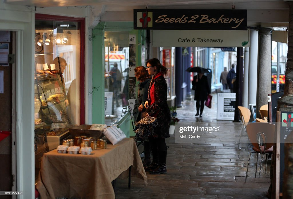 People browse in shops along the main shopping street of Totnes on January 8, 2013 in Totnes, England. The Devon town is renowned for its belief in promoting trade of local independent retailers, famously denying the plans by national coffee chain Costa to open a high street branch in the town. Boasting its own local currency, Totnes has a shop vacancy rate of 6%, less than half than the national average, whilst 80% of outlets are independently owned.