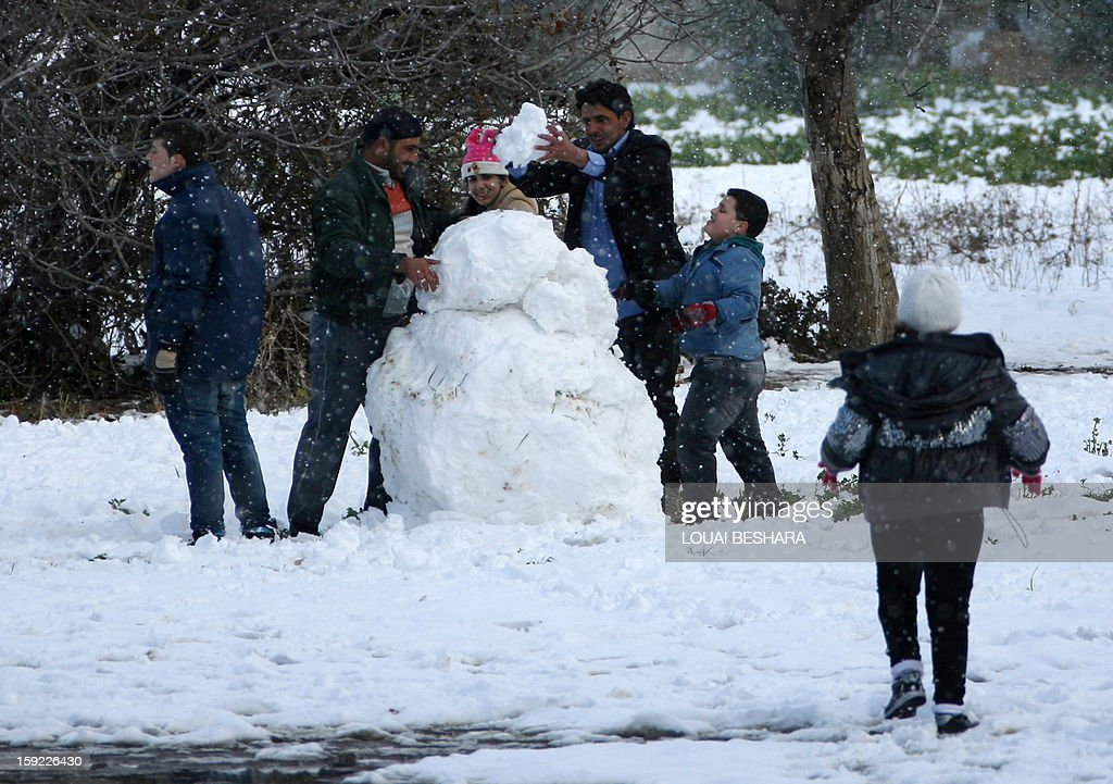 People build a snowman on January 10, 2013 in the Syrian capital of Damascus after heavy snow falls. Snow carpeted Syria's war-torn cities but sparked no let-up in the fighting, instead heaping fresh misery on a civilian population already enduring a chronic shortage of heating fuel and daily power cuts.