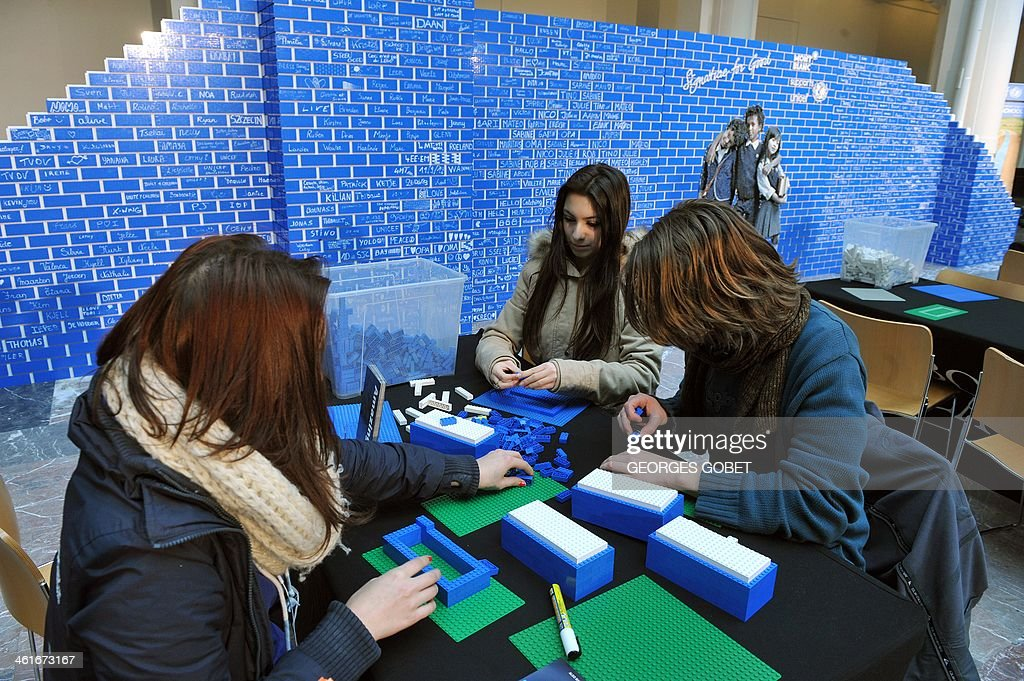 People build bricks made of Legos in front of a Lego wall as pupils and volunteers attempt to build the world's longest Lego wall at the Palais des Beaux-Arts in Brussels (BOZAR) on January 10, 2014. The event takes place until January 11 to support a UNICEF campaign to raise awareness about the need to construct new schools in developing countries.