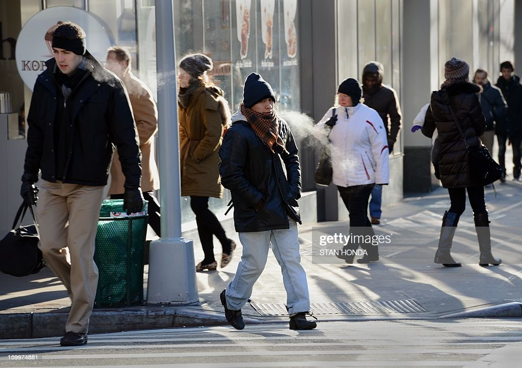 people, bundled for the cold, walk on the Upper East Side of Manhattan on a frigid morning, January 24, 2013 in New York. From the midwest to the East coast freezing temperatures have be responsible for several deaths. AFP PHOTO/Stan HONDA
