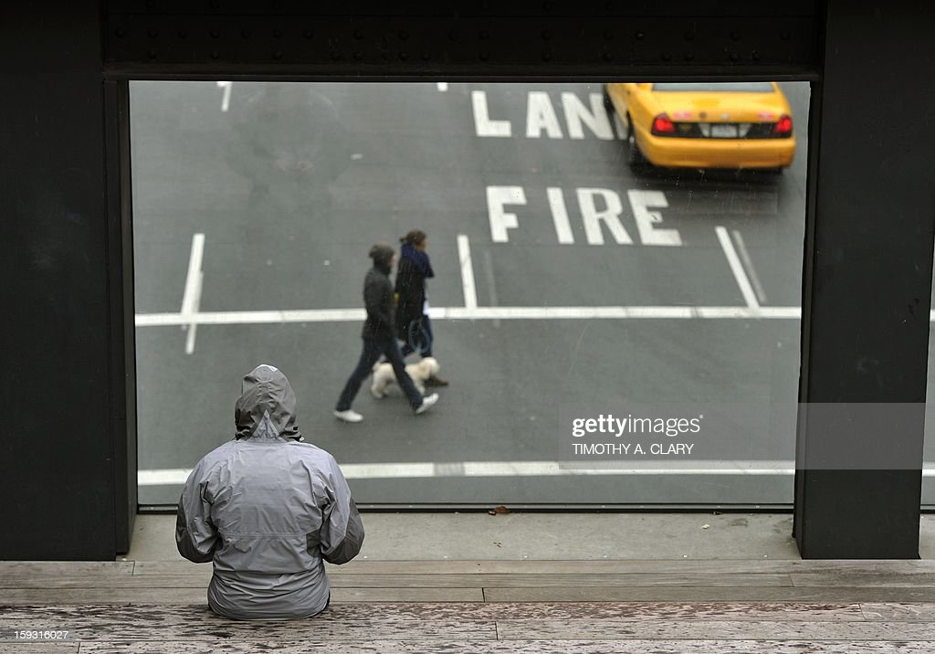 People bundled up in the cold watch cars go up 10th Avenue from a sitting spot on the High Line in New York on January 11, 2013. The High Line is a 1-mile New York City linear park built on a 1.45-mile section of the former elevated New York Central Railroad which runs along the lower west side of Manhattan.