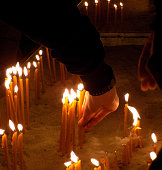People burn candles in the church