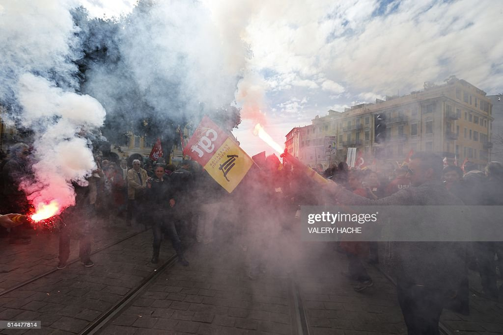 TOPSHOT People burn flares during a demonstration in Nice southeastern France on March 9 to protest the French government's planned deeply unpopular...