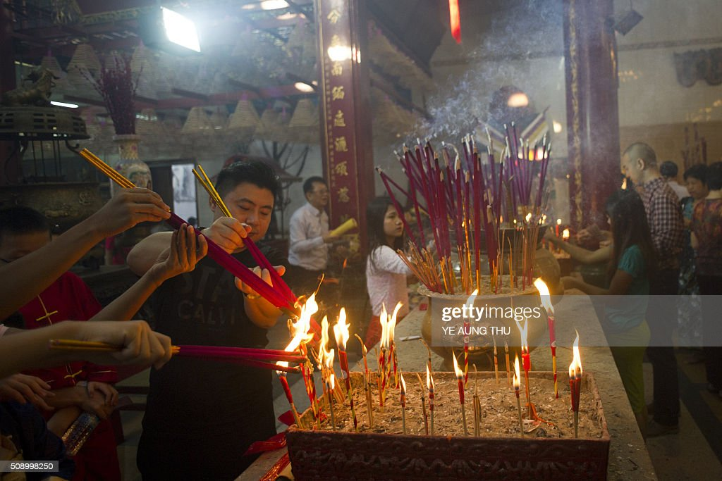 People burn incense and pray on the first day of the Lunar New Year of the Monkey at a temple at Yangon's Chinatown district on February 8, 2016. AFP PHOTO / Ye Aung THU / AFP / Ye Aung Thu