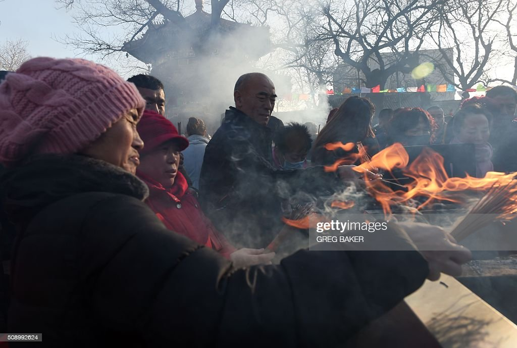 People burn incense for good luck at the Yonghegong Lama Temple on the first day of the Lunar New Year in Beijing on February 8, 2016. Millions of Chinese began celebrating the 'Spring Festival', the most important holiday on the Chinese calendar, which this year marks the beginning of the Year of the Monkey. AFP PHOTO / GREG BAKER / AFP / GREG BAKER