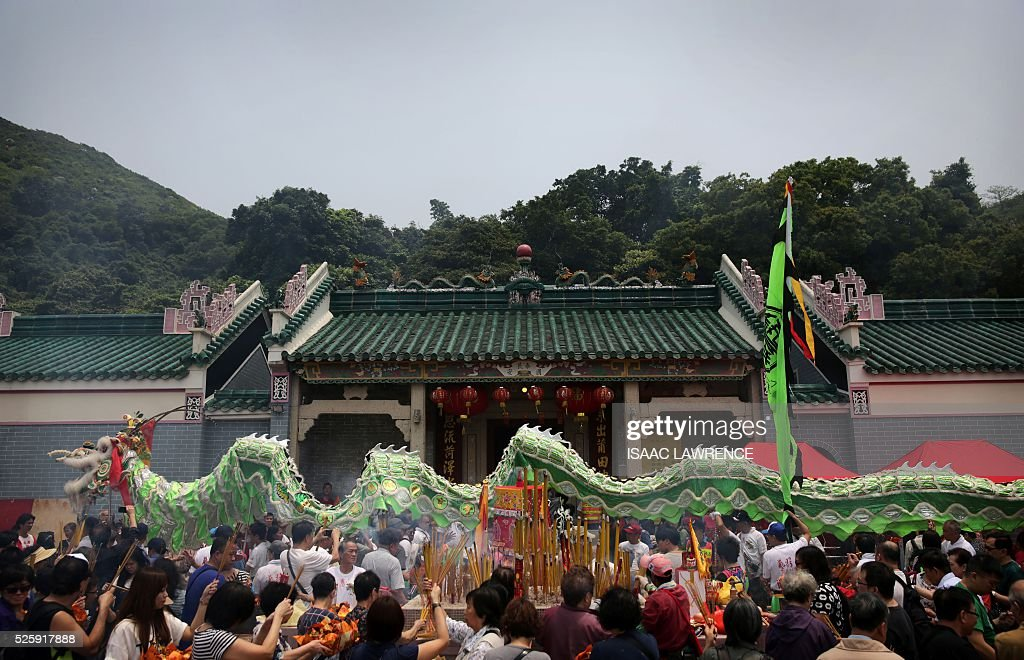 People burn joss sticks while a dragon dance happens outside the Joss House Bay Tin Hau temple during celebrations for the Tin Hau Festival in Hong Kong on April 29, 2016. Tin Hau is the Goddess of the Sea and patron saint of fishermen - On her birthday, locals flock to the more than 70 temples dedicated to her to pray for safety, security, fine weather and full fishing nets during the coming year. / AFP / ISAAC