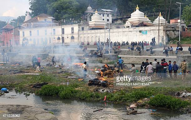 People burn the bodies of earthquake victims at a mass cremation at Pashupatinath in Kathmandu on April 26 2015 International aid groups and...