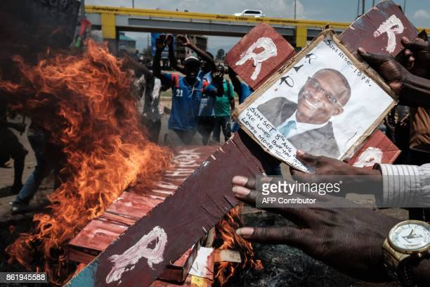 TOPSHOT People burn the fake coffin of Kenya's Independent Electoral and Boundaries Commission CEO Ezra Chiloba during a demonstration on October 16...