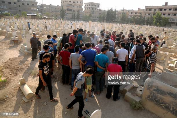People bury bodies of regime attack victims after Assad Regime's forces carried out their strikes over the deconflict zone Kafr Batna district in the...