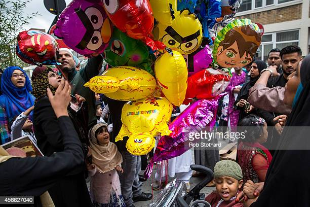 People buy balloons outside the East London Mosque after the Eid AlAdha prayers on October 4 2014 in London England Muslims around the world are...