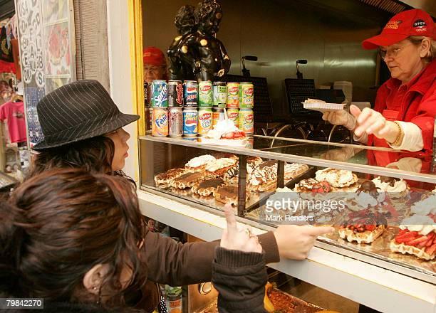 People buy Belgian waffles near la Grande Place on February 19 2008 in Brussels Belgium