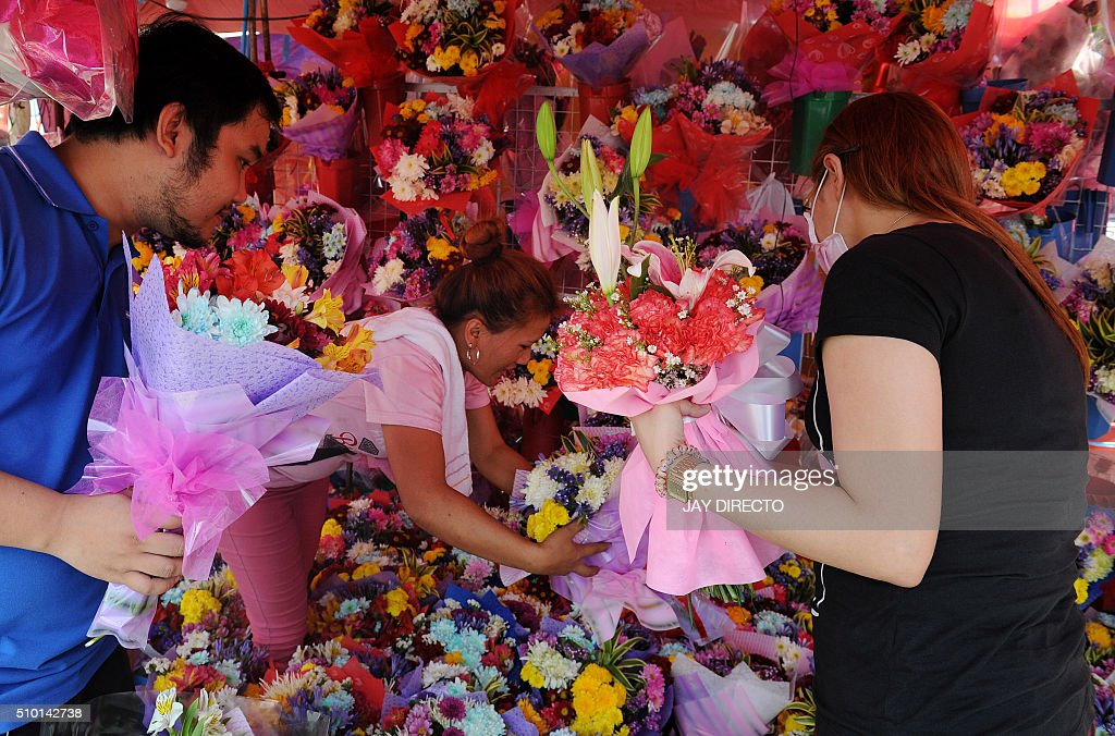 People buy bouquets of flowers at a street stall on Valentine's Day in Manila on February 14, 2016. Although not an official holiday, Valentine's Day is widely celebrated in this largely Christian nation with acts of affection and romance such as sweethearts going on special dates or giving expensive presents. AFP PHOTO / Jay DIRECTO / AFP / JAY DIRECTO