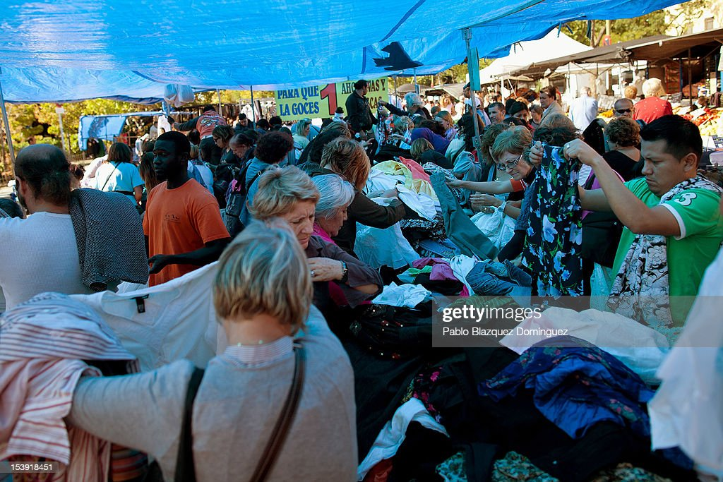 People buy clothes for the price of 1 Euro at a street market on October 11, 2012 in Madrid, Spain. Ratings agency Standard & Poor's has cut Spain's credit rating from BBB+ down to BBB-. The Spanish government has already introduced spending cuts and tax rises in an attempt to ease their debt and reduce their high unemployment levels. Spanish Economy Minister Luis de Guindos maintains that his country will not need to ask for a bailout.
