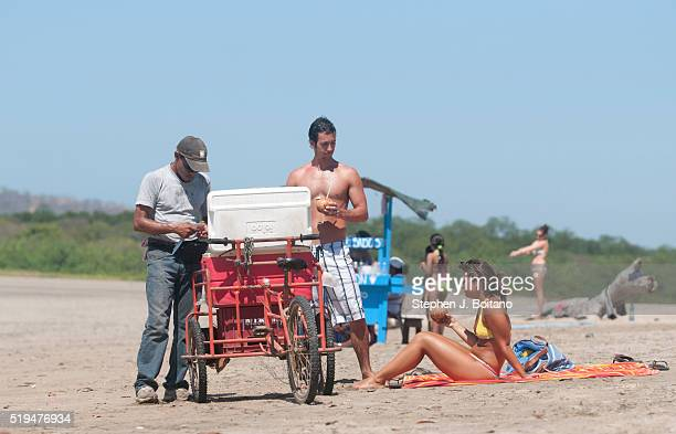 People buy coconuts from a vendor on the beach at Playa Tamarindo in Costa Rica