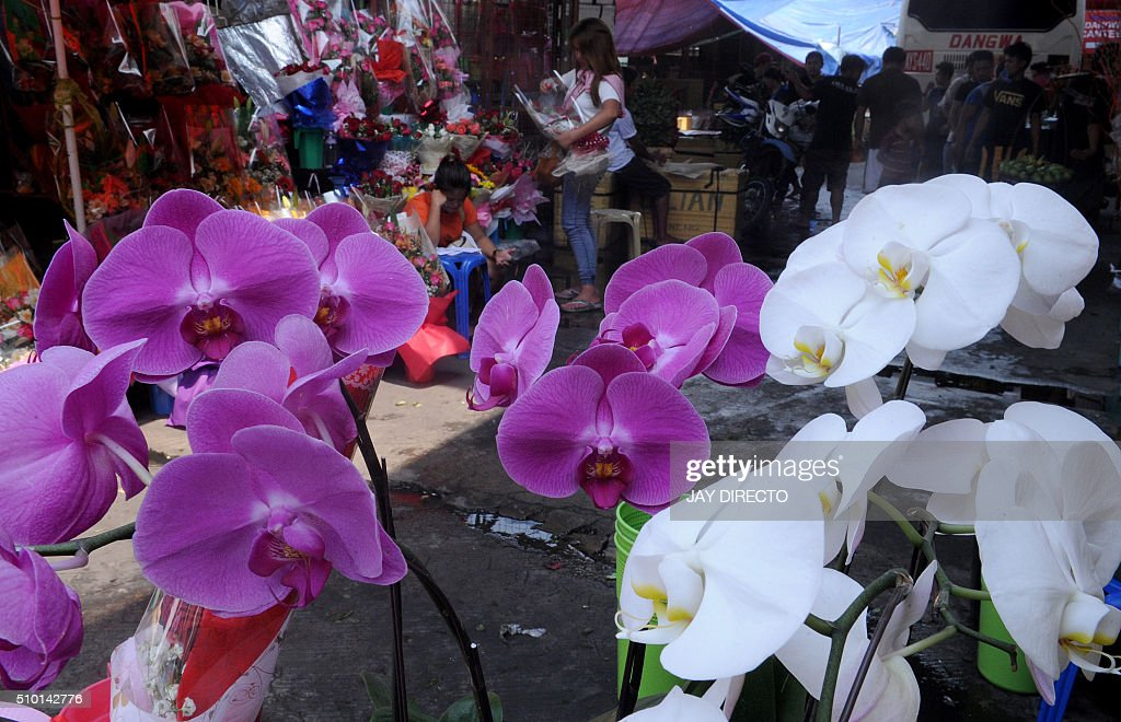 People buy flowers at a street stall on Valentine's Day in Manila on February 14, 2016. Although not an official holiday, Valentine's Day is widely celebrated in this largely Christian nation with acts of affection and romance such as sweethearts going on special dates or giving expensive presents. AFP PHOTO / Jay DIRECTO / AFP / JAY DIRECTO