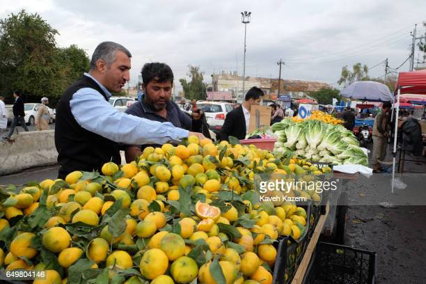 People buy fruit and green grocery from vendors in the market place near the citadel on November 2 2016 in Erbil Iraq Erbil also spelt Arbil or Irbil...
