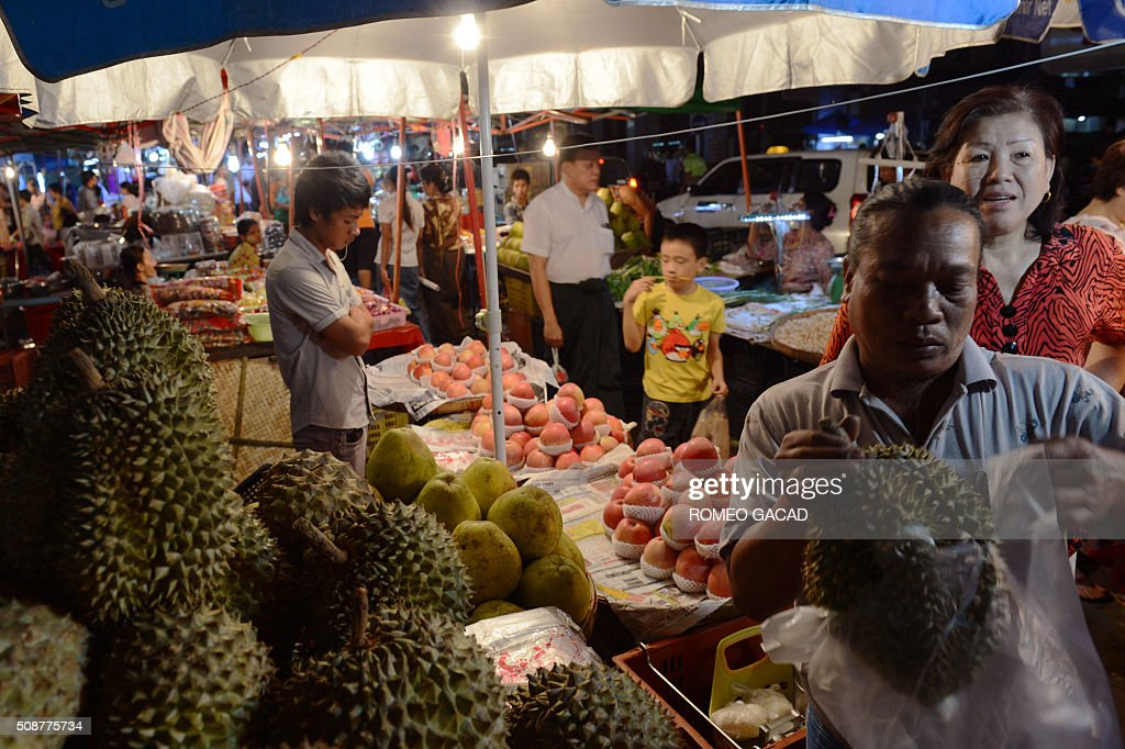 People buy fruits during last minute rush in Yangon's Chinatown district on February 6, 2016 in preparation for the Lunar New Year celebrations which falls on February 8 and will mark the start of the year of the monkey. / AFP / ROMEO GACAD