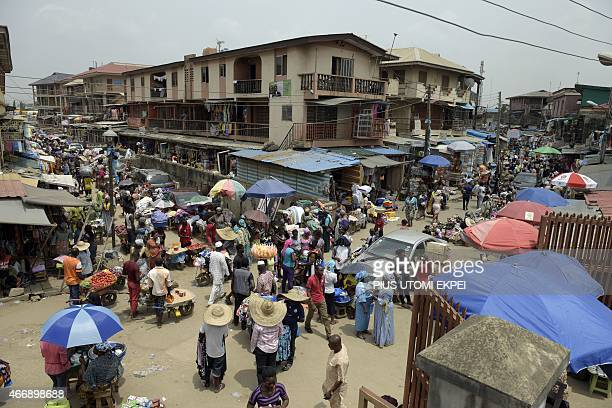 People buy goods at Oshodi market in Lagos on February 25 2015 Congested streets lined with shops selling everything from plastic sandals to instant...