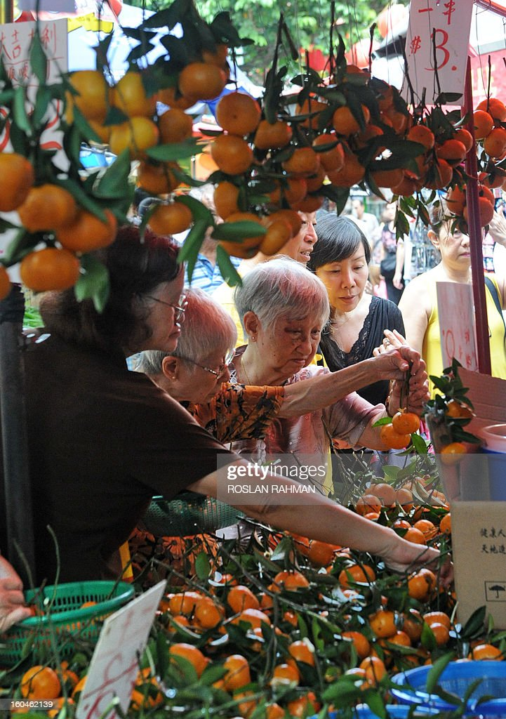 People buy mandarin oranges at a bazaar for the upcoming Chinese lunar New Year of the snake in Chinatown of Singapore on February 1, 2013. Chinese celebrate the Chinese lunar New Year of the snake on February 10.
