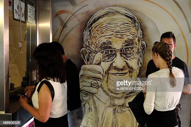 CAPTION === People buy tickets at a counter next to an official painting by French street artist Christian Guemy aka C215 representing Pope Francis...