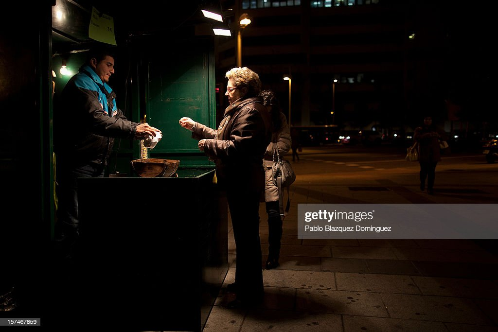 People buys chestnuts from a street vendor at Plaza de Castilla on December 3, 2012 in Madrid, Spain. Spain has formally requested 39.5 euro billions bank bail-out of European funds. Economy Ministry of Spain, Luis de Guindos said that 37 euro billions will be paid for the four nationalized banks Bankia, Catalunya Banc, NCG Banco and Banco de Valencia while 2.5 euro billions will be for the 'bad banks'.