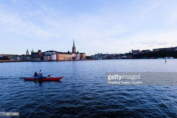 People Canoeing In River By City Against Sky