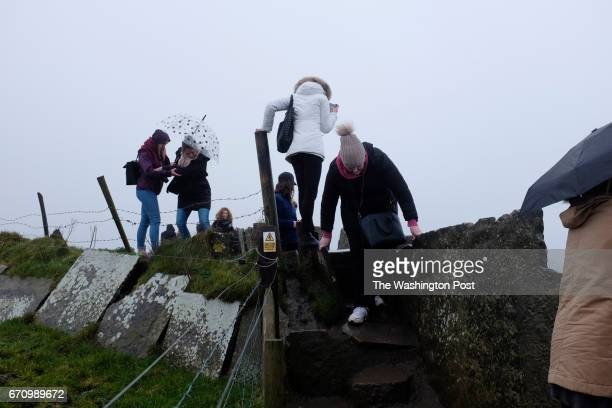 People carefully walk along the path near the edge of the Cliffs of Moher