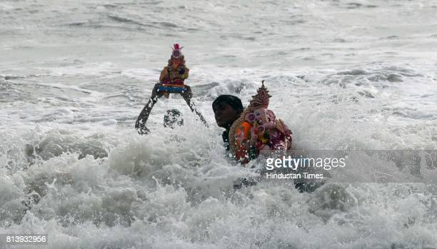 People carries an idol of Hindu God Ganesha for immersion in the Versova sea on the fifth day at Versova in Mumbai on MondayHt