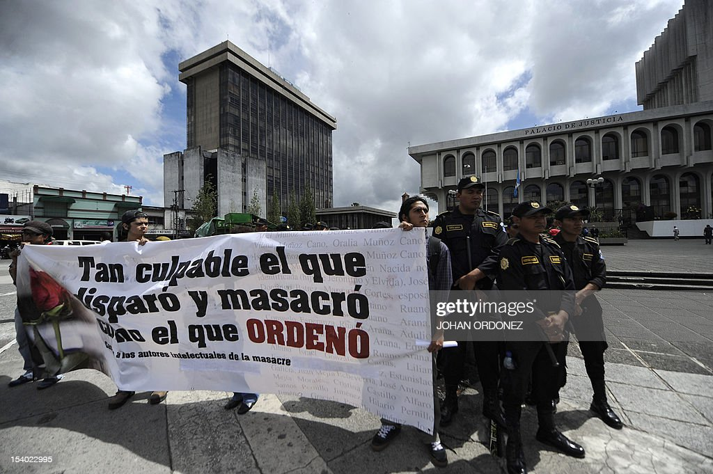 People carry a banner reading 'He who shot and massacred is as guilty as he who ordered it' during a protest in Guatemala City on October 12 2012 The...