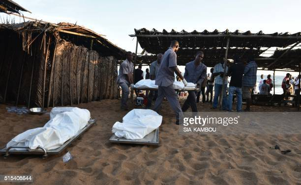 TOPSHOT People carry a body on a stretcher following after gunmen went on a shooting rampage in the Ivory Coast resort of GrandBassam on March 13...