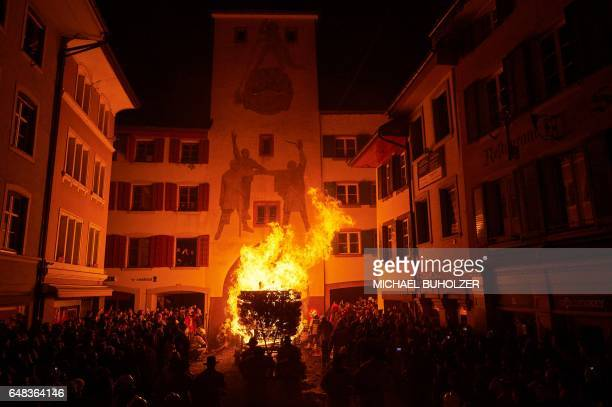 TOPSHOT People carry a burning wooden wagon loaded with bundles of pinewood chips pass the old city gate during the 'Chienbase' procession on March 5...