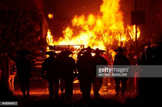 People carry a burning wooden wagon loaded with bundles of pinewood chips during the 'Chienbase' procession on March 5 2017 in Liestal northern...