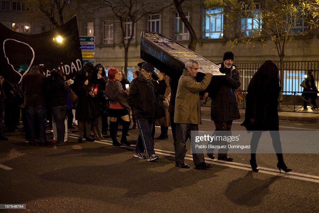People carry a cardboard coffin during a protest mourning the public health system on December 4, 2012 in Madrid, Spain. Trade unions called for the second 48-hour health workers' strike in the Madrid region, after the regional government announced severe cuts and privatization of medical centers.