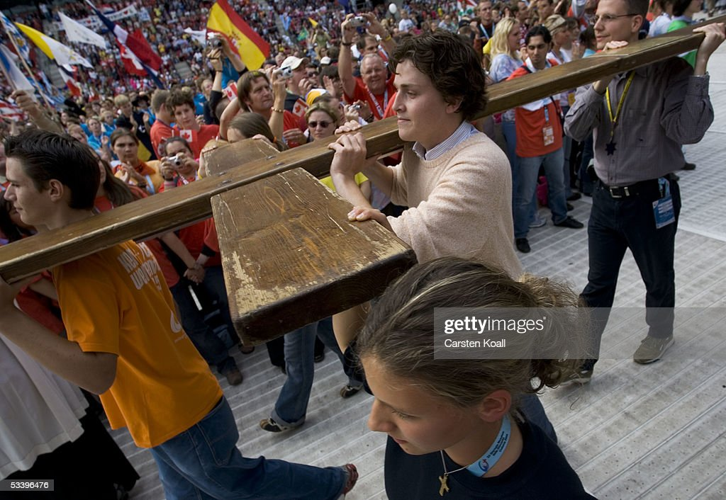 People carry a cross at World Youth Day to the opening mass at the RheinEnergie Stadium August 16, 2005 in Cologne, Germany. Thousands of young Catholics are arriving in Germany on the first day of the World Youth Day with Pope Benedict XVI, culminating in an open-air mass on August 21 which is expected to attract 800,000 worshippers from 193 countries.