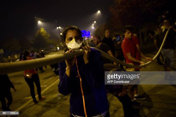 TOPSHOT People carry a hose to help fighting a wildfire in Vigo northwestern Spain on October 15 2017 Hundreds of firefighters struggled on October...