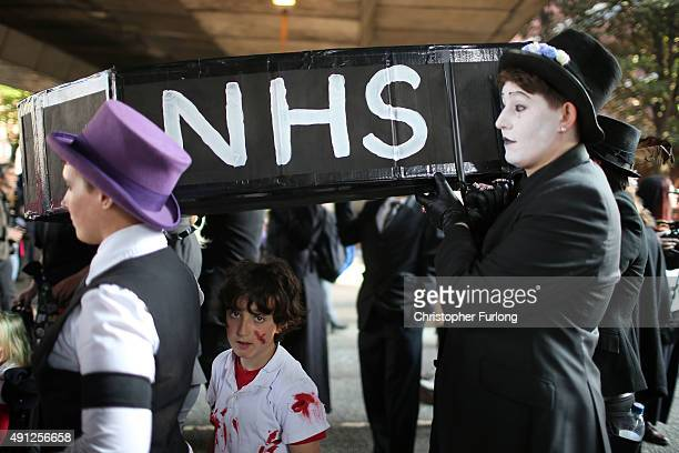 People carry a mockup of a coffin with the letters 'NHS' on the side as they take part in an antiausterity protest during the first day of the...