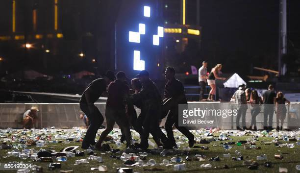 People carry a person at the Route 91 Harvest country music festival after apparent gun fire was heard on October 1 2017 in Las Vegas Nevada There...