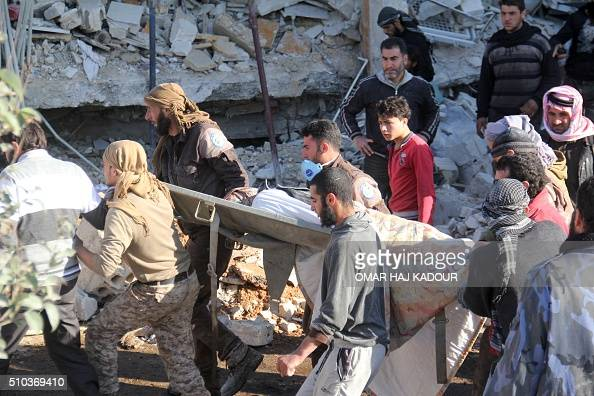 People carry a stretcher amidst debris after a hospital supported by Doctors Without Borders was hit by suspected Russian air strikes near Maaret...