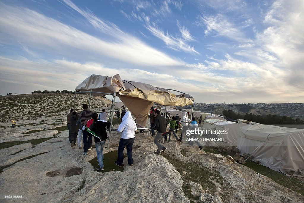 People carry a tent at an 'outpost' named Bab al-Shams ('Gate of the Sun') that Palestinian activists set up between Jerusalem and the Jewish settlement of Maale Adumim in the Israeli-occupied West Bank, in an area where Israel has vowed to build new settler homes, on January 12, 2013. The Israeli occupation administration gave Palestinian activists an ultimatum to quit the protest camp in part of the West Bank, but hours after the deadline passed, there was no sign of any Israeli move to evict the protesters.