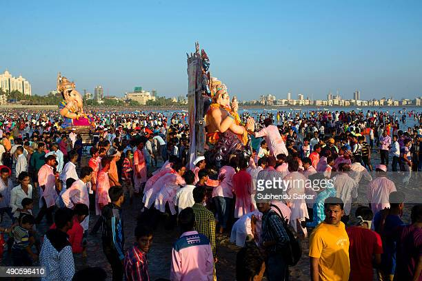 People carry an idol of lord Ganesha for immersion into the Arabian sea at Girgaum Chowpatty in Mumbai Ganesha Chaturthi or Ganapati festival is...