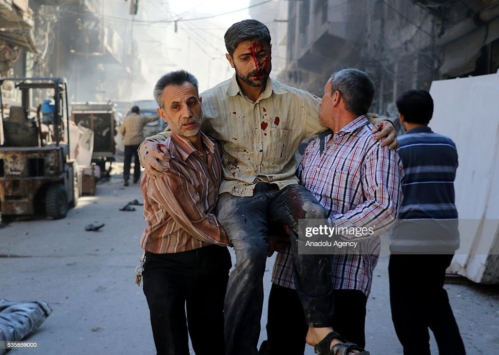People carry an injured man after Syrian forces air-strike over Aleppo's opposition controlled Kellese district, Syria on May 30, 2016. 15 people were killed and another 24 injured when a Syrian regime forces attack.