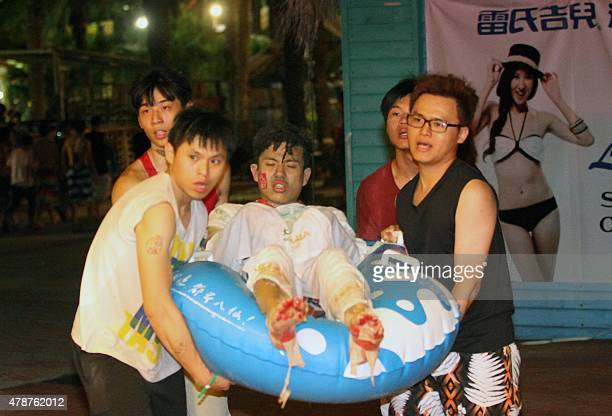 People carry an injured man at the Formosa Fun Coast amusement park after an explosion in the Pali district of New Taipei City on June 27 2015 More...