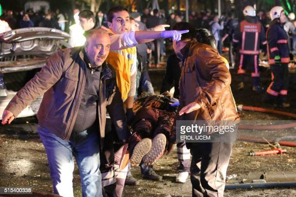 TOPSHOT People carry an injured person on a stretcher at the scene of a blast in Ankara on March 13 2016 An explosion ripped through a busy square in...
