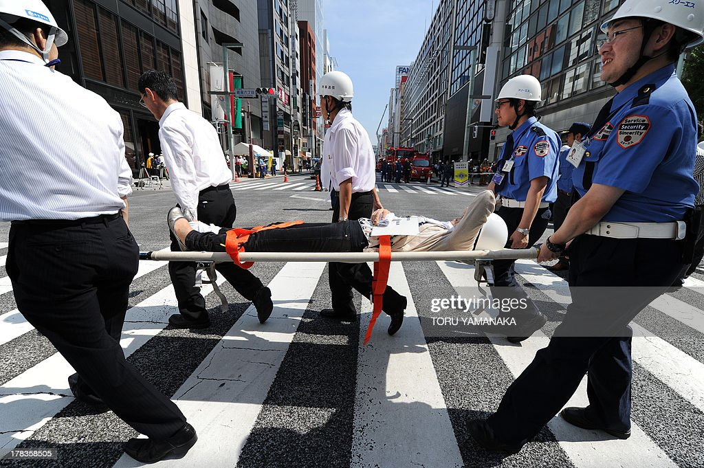 People carry an injured person on a stretcher during a disaster drill at Ginza shopping district in Tokyo on August 30, 2013. Some 5,000 people who live or work in the district, took part in the annual drill. AFP PHOTO/Toru YAMANAKA