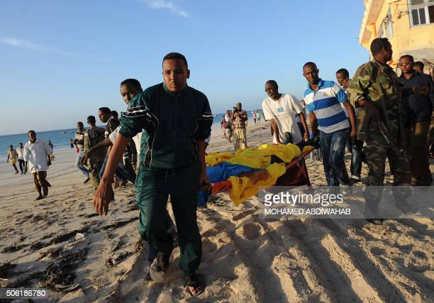 People carry away a dead body from the Lido beach following an overnight attack on the beachfront Lido seafood restaurant in Mogadishu on January 22...