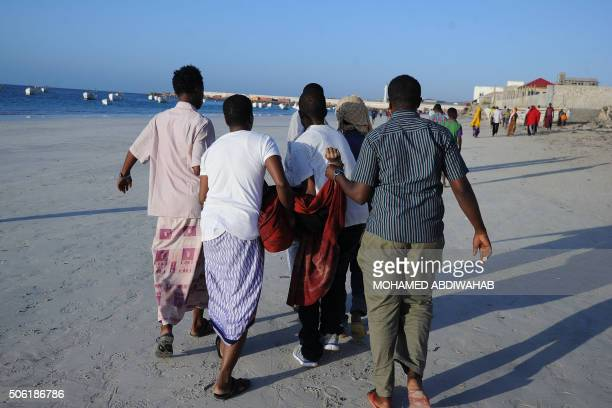 TOPSHOT People carry away a dead body from the Lido beach following an overnight attack on the beachfront Lido seafood restaurant in Mogadishu on...
