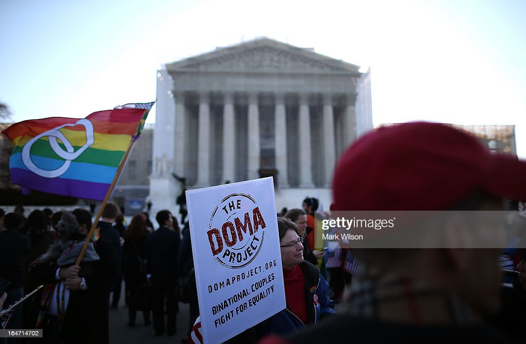 People carry banners and flags during a rally in front of the U.S. Supreme Court, on March 27, 2013 in Washington, DC. Today the high court is scheduled to hear arguments on whether Congress can withhold federal benefits from legally wed gay couples by defining marriage as only between a man and a woman.