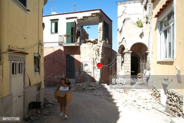 People carry belongings from they damaged homes in Casamicciola Terme on the Italian island of Ischia on August 22 after an earthquake hit the...